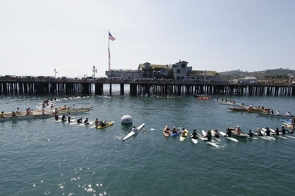 """Paddle Out participants in a """"healing circle"""" next to Stearns Wharf."""