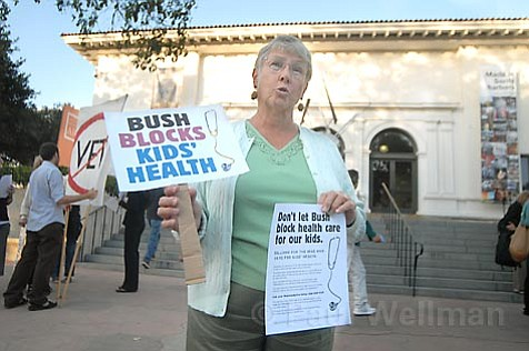 A MoveOn member protesting Bush and encouraging elected officials to override his veto.