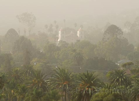 Pushed by heavy winds, ash from this summer's Zaca Fire poured into the South Coast on Saturday, leaving Santa Barbara's air unhealthy to breathe and everything else covered with a layer of soot.