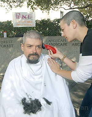 Santa Barbara resident Holden Smith gets his head shaved by performance artist Genevieve Erin O'Brien on Friday in downtown Santa Barbara.