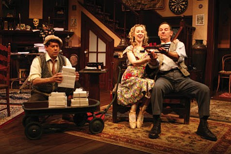 Ed Carmichael (Joseph Fuqua) prepares a candy delivery while his wife, Essie (Sonia Sanz), and her father, Paul Sycamore (Leonard Kelly Young), play with a toy boat.