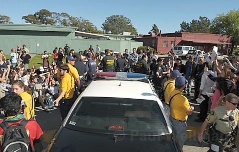 Protesters lock arms surrounding the police car detaining arrested activist Michael Miller.