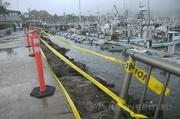 Across from the S.B. Yacht Club, Sunday's waves crashed across the breakwater and threw a woman through the metal railing and into the harbor