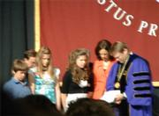 After receiving an inauguration medal, Gayle Beebe prays with his family.