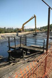 A Federal Environmental Protection Agency-run clean-up effort tackles an oil-choked storage pool-caused by a busted pipe-just off Palmer Road, a few miles north of Los Alamos.