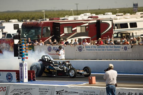 A driver does a burn-out before the race, which is done to heat the tires for better traction.