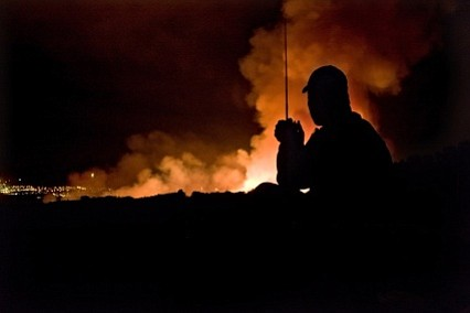 Fleming Bertelsen, a Fire Investigator with the U.S. Forest Service, keeps his team informed of changes in the fire from his view on West Camino Cielo Road. This photo was taken at about 3:15 a.m.