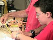 Nine-year-old Marshall Payatt helps Eric Hochberg examine the giant squid.