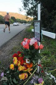 Passing on: A man runs by a memorial for Carolyn Samuels.