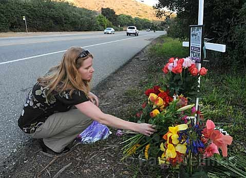 Jaimi Kercher sets flowers at the memorial for Carolyn Samuels, a 66-year-old woman killed by an alleged drunken driver. Family members remember the woman as a compassionate mother and grandmother.