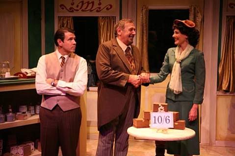 Mr. Maracek (George Ball) congratulates Amalia (Kim Huber) on her new job, while Georg (Kevin Symons) looks on skeptically.