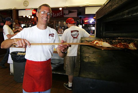 Manager John Henning gets ready to serve up one of Deano's Pizzarama's delicious pies.