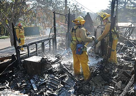 Los Angeles County firefighters mop up the remains of a home in Las Barrancas, a neighborhood where many Westmont College faculty live.