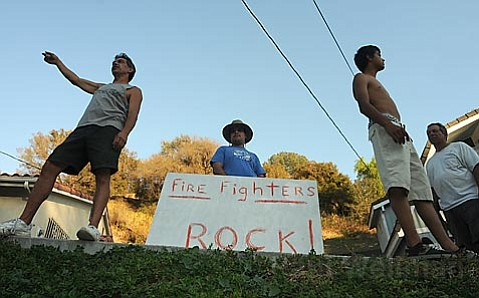Michael Ovieda (left) and family are staying put at their Sycamore Canyon Road residence despite flames getting close.