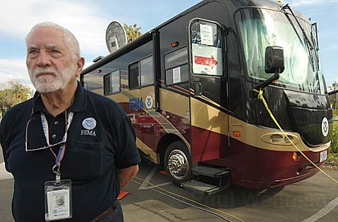Don Daniel, a FEMA public information officer, stands in front of FEMA's Mobile Disaster Recovery Center.
