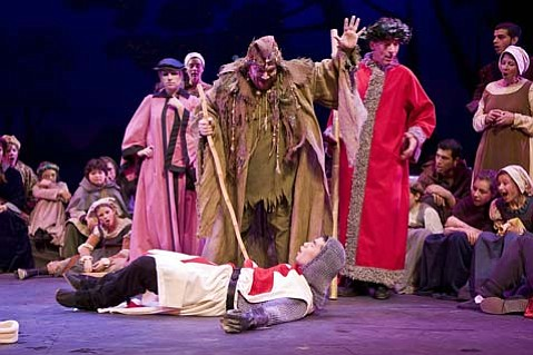 "The ""St. George and the Dragon"" mummers play from <em>The Christmas Revels</em>. From left to right, surrounded by singers, Christy Flis as the Doctor, Ken Ryals as the Fool, and David Brainard as the Lord. At their feet, St. George."
