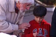Jean-Michel Cousteau educating a youngster about the harms of plastic shopping bags to the environment.