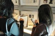 Students study photos and stories from the Portraits of Survival exhibit