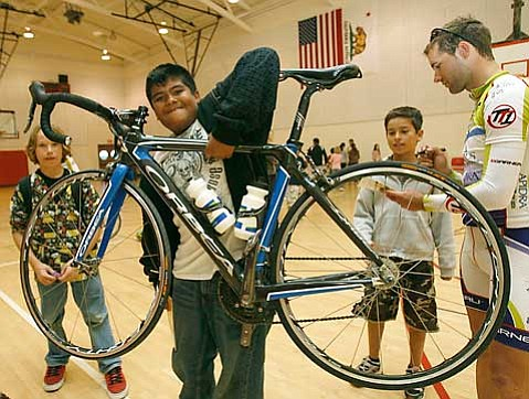 Javier Guerrero, a fifth grader at Solvang Elementary School, lifts up Daniel Holt's bike as the cyclist signs autographs after an assembly last week.