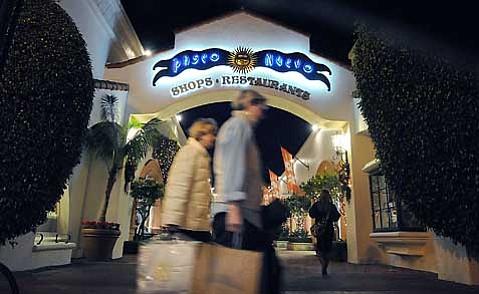 Shoppers skitter around State Street's Paseo Nuevo.
