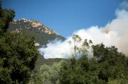 Though fire is less than a half acre in size, winds quickly push it east.