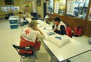 Red Cross Shelter volunteers  Janet Napier (left) and Harley Hahn chat in wee hours of a slow night at the Dos Pueblos High School Gym. Out of all the evacuated ares only 10 people came in seeking shelter.