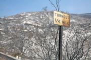 Sign along Highway 154 depicts damage done during Friday evening's fire run towards Painted Cave.