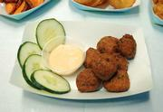 Fresh-made falafels served with cucumber slices and spicy, creamy peanut dipping sauce.