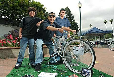 """Christian Solis (center) poses on his bike """"Chameleon"""" with brother Enrique (left) and Riding Low Bike Club president Juan Montero (right) during the Lowrider Festival at Earl Warren Showgrounds"""