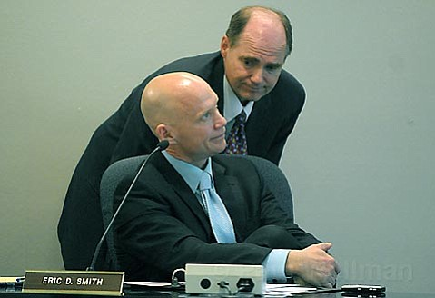 <strong>Budget Brainstorm: </strong> Superintendent Brian Sarvis (standing) and Deputy Superintendent Eric Smith huddle up at the start of Tuesday's School Board meeting, trying to find a less painful way to once again cut from the district's general fund.