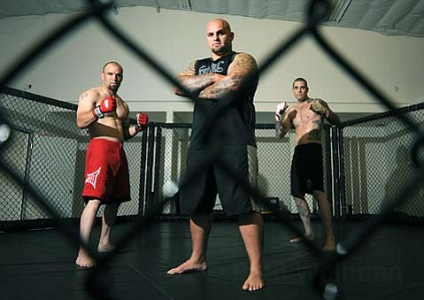 Flanked by fighters Critter (left) and Shannon Good (right), Santa Barbaran Anthony Arria (center) brings mixed martial arts matches to town.