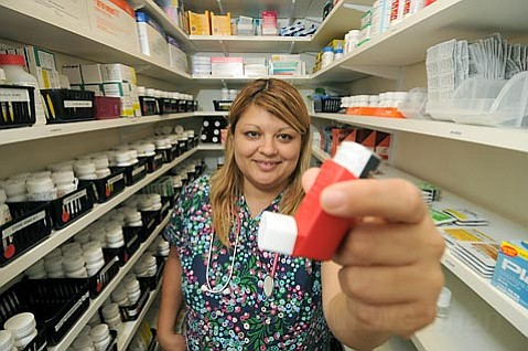 Ivanessa Guerreroa, a medical assistant at the Eastside Neighborhood Clinic, holds an asthma inhaler, one of the many medical supplies donated by DRI