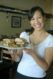 Server Meagan Mori presents a grilled chicken sandwich with fries at Jane.