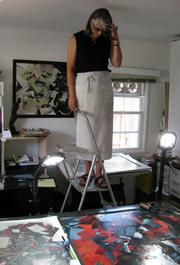 Photage artist Marlene Struss on her studio ladder looking down at her photage work.