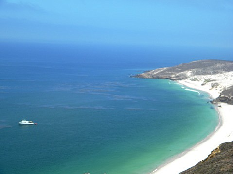 A shot of the beach and the clear blue water, and a bit of the sand dunes that exist on San Miguel island.