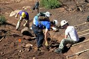 During first part of creating a dip, workers fill in the gully with rock to armor it.