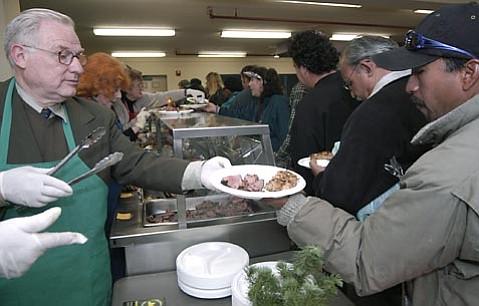 Roger Heroux works the serving line at Casa Esperanza on December 1, 2003.