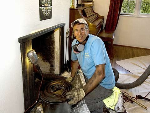 George Murdoch inspecting and cleaning a fireplace.