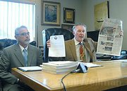 "Jerry Robert's attorney Dennis Merenbach holds up the News-Press ""front page smear"" in 2007"