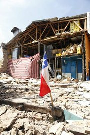 A Chilean flag sticking out of the rubble on a destroyed property in Talca.