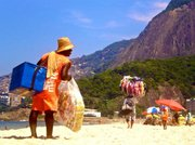 A vendor of the Carioca snack dream team - Matte Leão and Biscoitos Globos, looks for potential customers while a bikini vendor paces ahead of him.