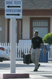 Santa Barbara Police officer Warren Holtke, working on detail with the Santa Barbara Sheriff's Bomb Squad, carries the suitcase deemed no longer a threat from the DMV.