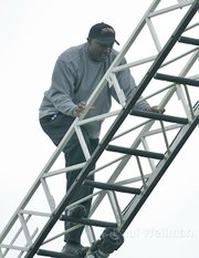 "Tim Brown climbs the ladder of a SB City fire truck to veiw the ""81"" formation on the Notre Dame playground"