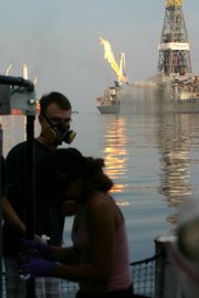 Research scientists aboard the RV Cape Hatteras at work. The oil capture rig, Discovery Enterprise, can be seen in the background.