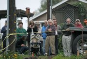 Art Gaspar (center with arms folded) watches with neighbors as construction crews work on his new modular home