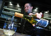 Jeffrey Parker, a bartender at the Hadsten House Inn and Spa, pours a glass of Bridlewood Chardonnay at the Hadsten House's restaurant during wine tasting hours.