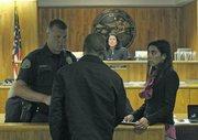 Officer Keld Hove and Jennifer Archer counsel a Restorative Court participant.