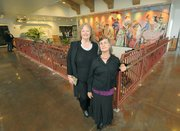 Posing in front of a mural painted in 1984 by the late Channing Peake is his wife Cheri Peake (left) and daughter Tuni Peake during the Santa Barbara Airport remodel grand opening celebration  June 17, 2011