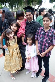 Graduate Carmelo Medina is surrounded by family and friends following the end of the commencement ceremony.