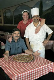 Petrini's owner Joe Bohnett (seated) Victoria Browning (server) and Manny Ortiz (cook)